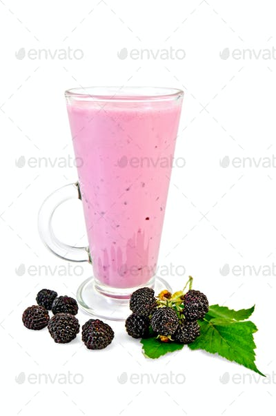 Milkshake in a tall glass with blackberry and leaf