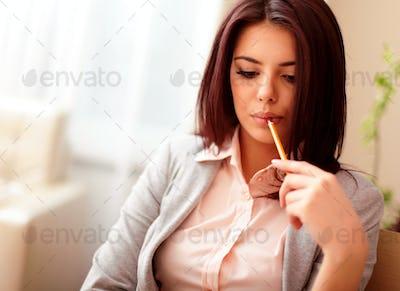 Portrait of a young pensive businesswoman holding a pencil