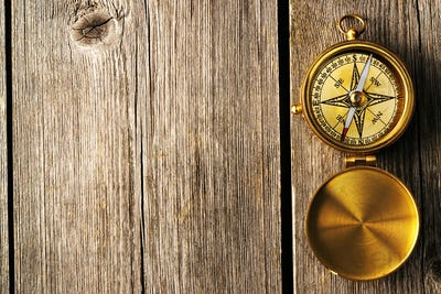 Antique compass over wooden background
