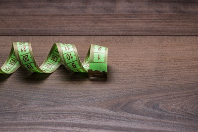 Green Measuring Tape On Wooden Background