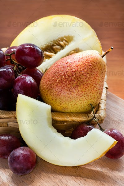 Fresh fruits in basket over wooden  background