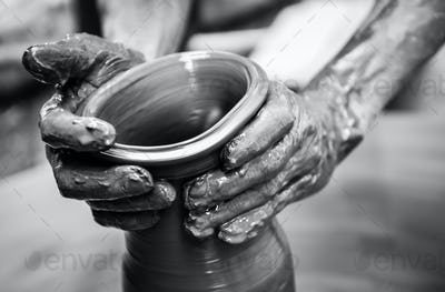Hands of a man creating pottery on wheel