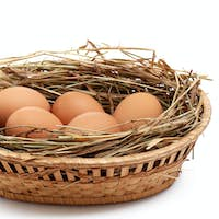 Chicken eggs and hay in  the brown basket .