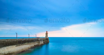 Pier and lighthouse on sunset, Fecamp harbor. Normandy France.