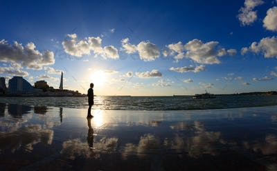 Silhouette of a boy on the seafront