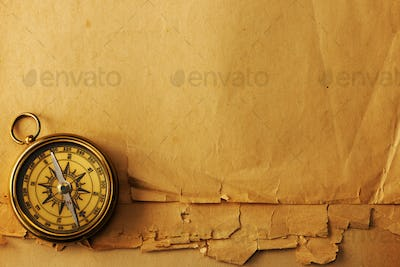 Antique brass compass over old background