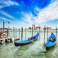 Venice, gondolas or gondole and church on background. Italy
