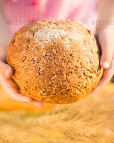 Child holding bread in hands