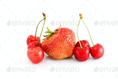 Single tasty red strawberry and some juicy red cherries