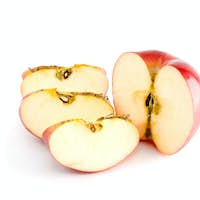 Red apple half and three pieces