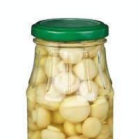 Glass jar with marinated white mushrooms