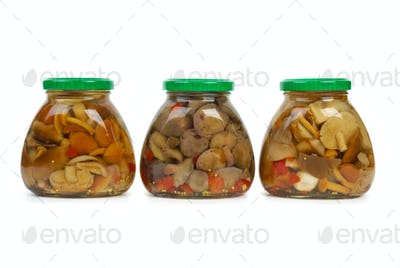 Three glass jars with marinated mushrooms