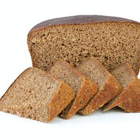Half of rye bread loaf and few slices