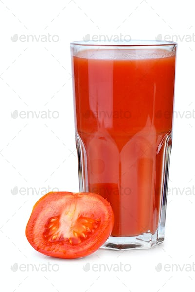 Drinking glass with tomato juice and ripe fresh tomato near
