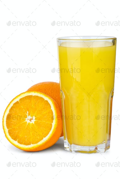 Drinking glass with orange juice and oranges near