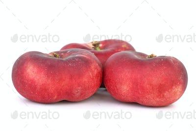 Three red flat peaches