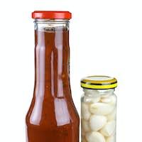 Bottles with tomato ketchup and marinated garlic