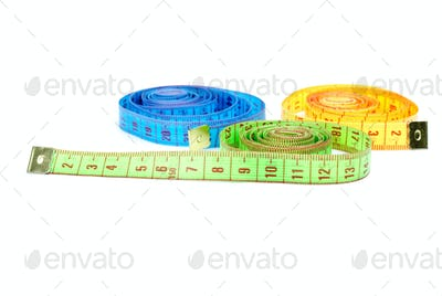 Three rolled measuring tapes of different colors