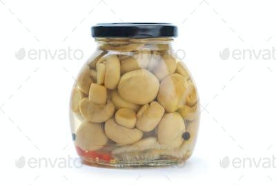 Glass jar with marinated champignons