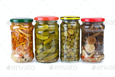 Glass jars with marinated cornichons, mushrooms and capers
