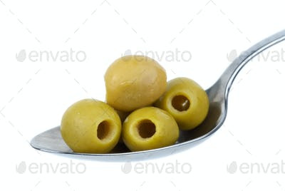 Five marinated pitted green olives in the metal spoon