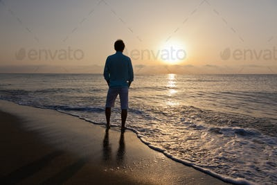 Alone caucasian man standing on beach watching the sunrise.