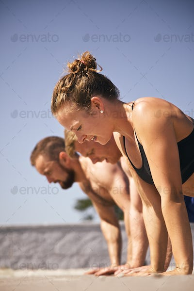Group of people doing push-ups on beach