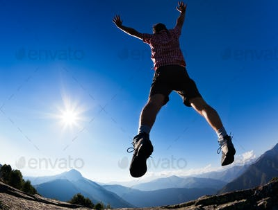 Man jumping in the sunshine against blue sky