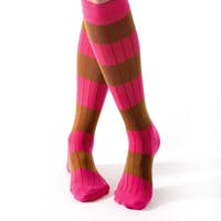 Young woman crossed legs posing with pink striped socks