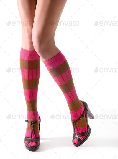 Young woman legs posing with pink striped socks and sandals