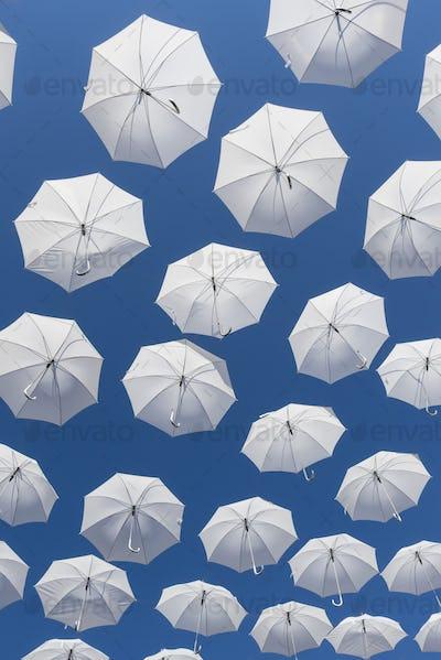 White umbrellas on blue sky
