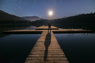 Man Looking At Moon on Dock in Whistler