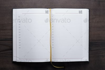 Opened Notebook On The Wooden Table