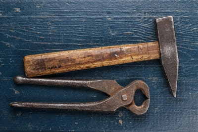 Tongs And Hammer On Blue Table