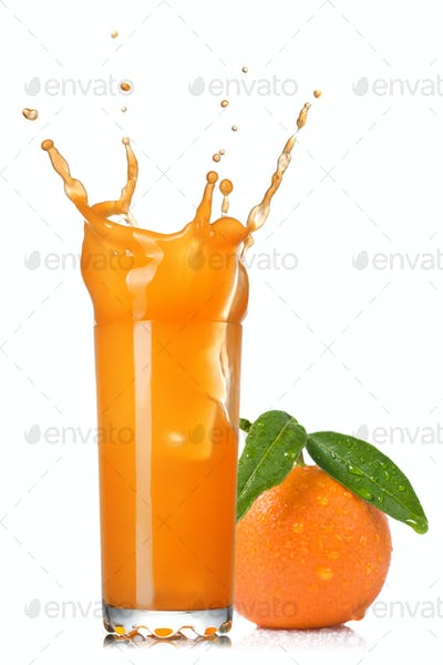 orange juice splash in glass with tangerine isolated on white