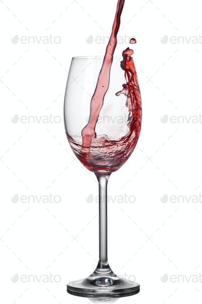 Splash of wine in wineglass on white