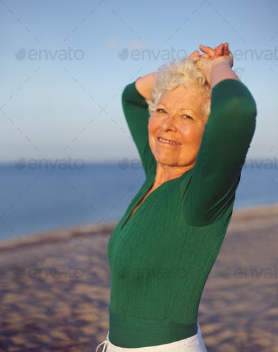 Beautiful senior woman standing relaxed at the beach