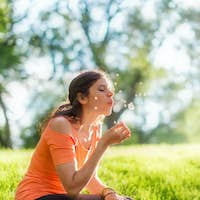 Portrait of a girl in nature blowing  a dandelion