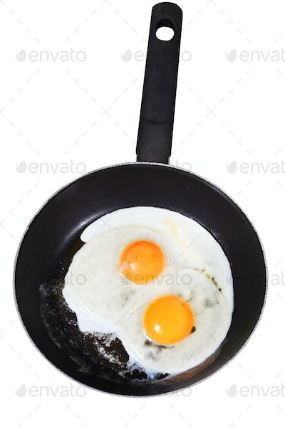 fried eggs in frying pan isolated on white