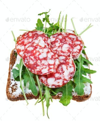sandwich from salami, grain bread and arugula