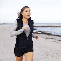 Fit and healthy woman jogging on beach