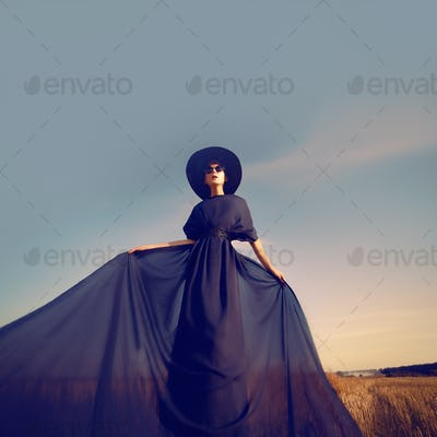 Sensual portrait of a girl in a black dress in the forest