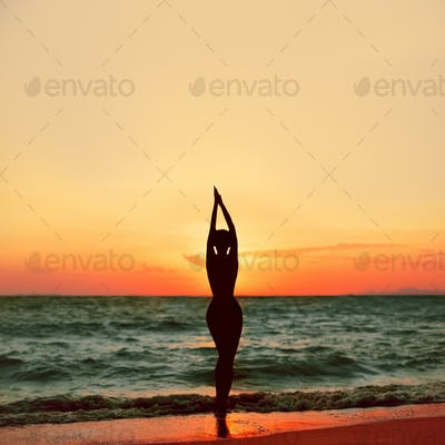Beautiful slim girl at sunset on the beach