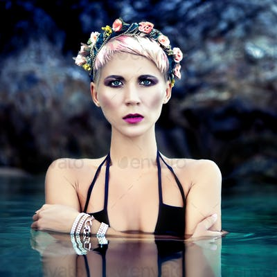 sensual girl in a wreath of flowers in the sea