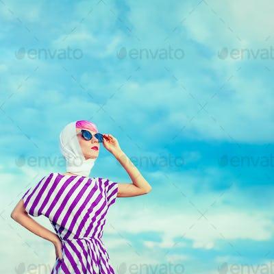 Portrait of retro girl on the blue sky