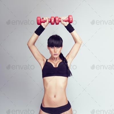 sporty muscular woman working out with two dumbbells