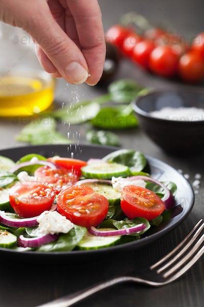 hand adding salt to vegetable salad