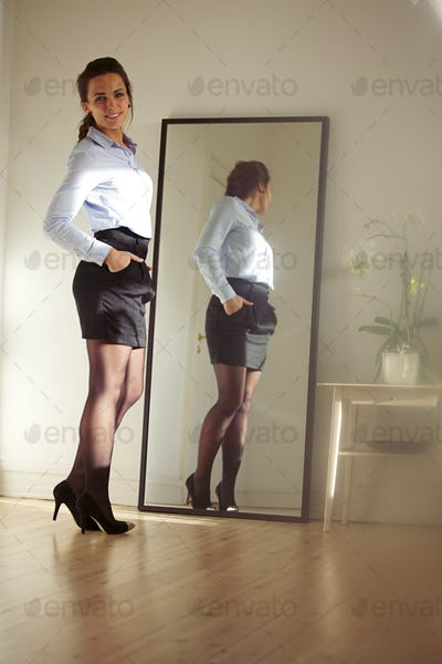 Confident young businesswoman posing in front of mirror