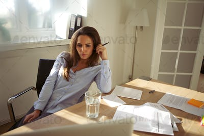Beautiful young woman with laptop working from home