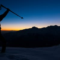 Winter hiking: man stands on a snowy ridge looking at the sunset.
